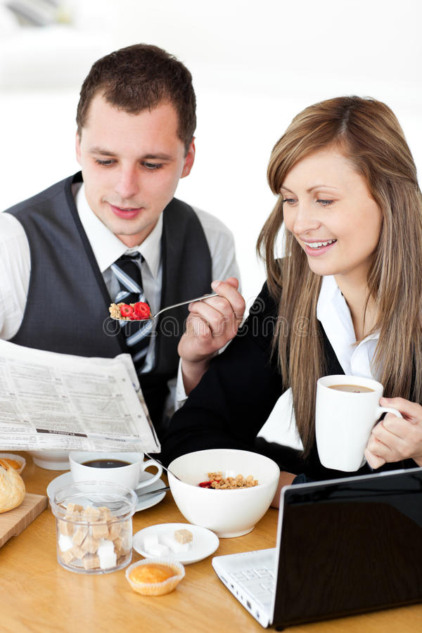 Positive businesspeople having breakfast reading