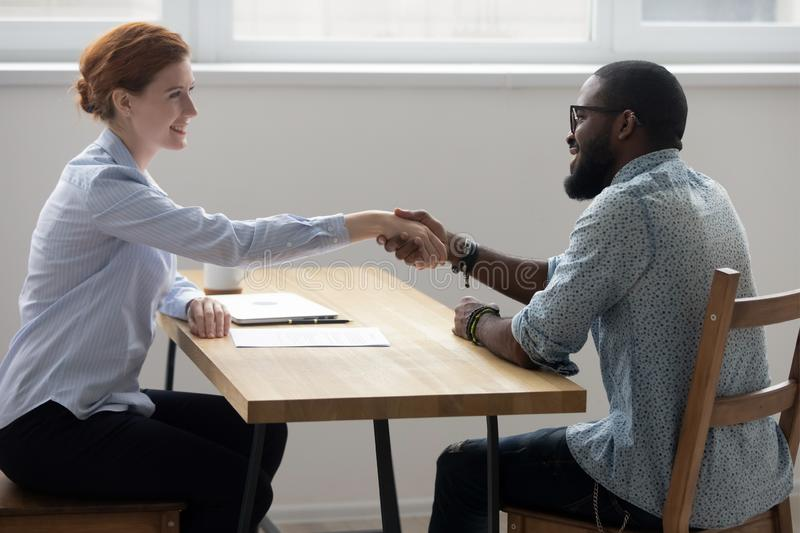 Positive businesswoman handshaking with black businessman in boa royalty free stock photo