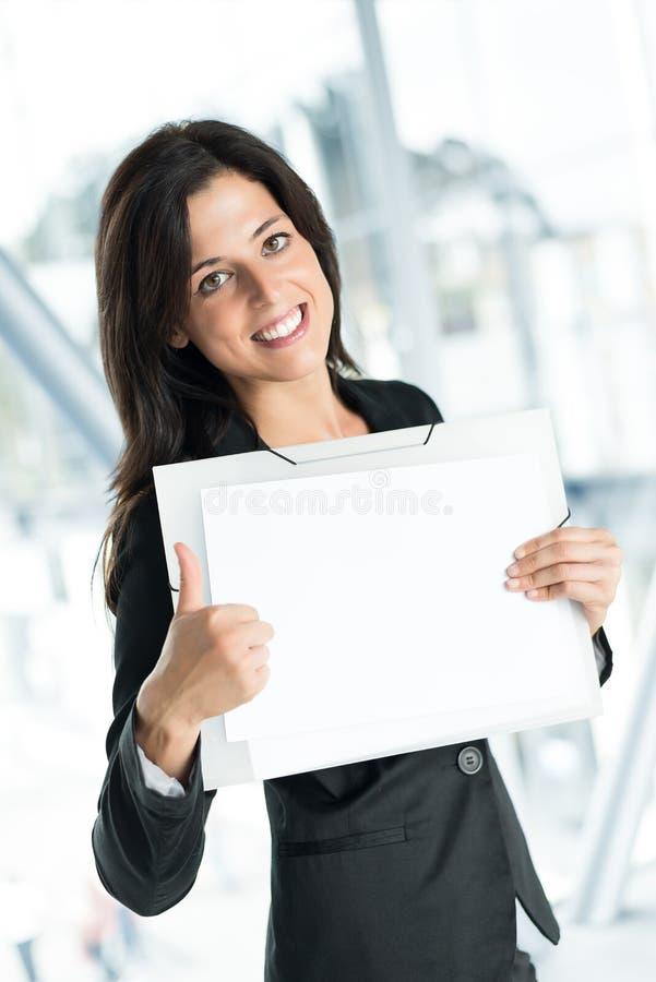 Positive businesswoman holding blank banner stock photo
