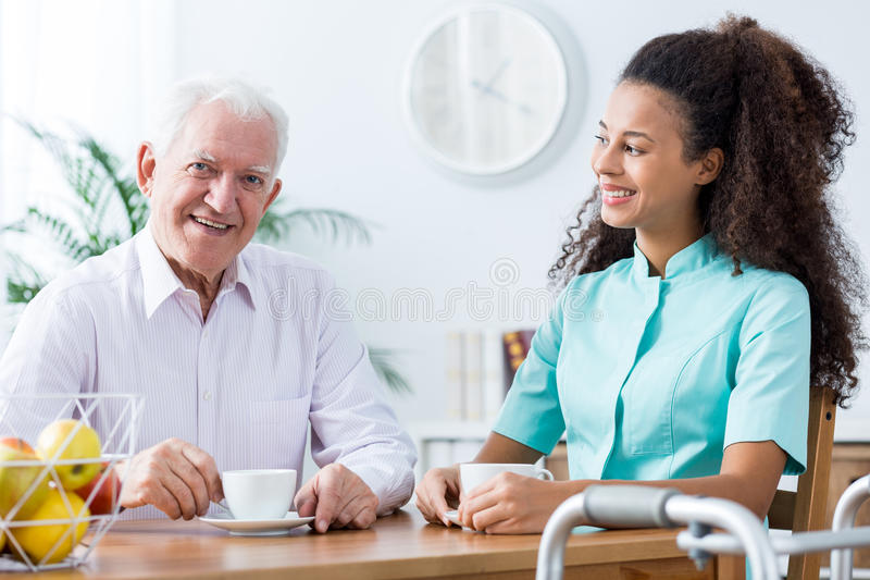 Positive carer and retired man stock image