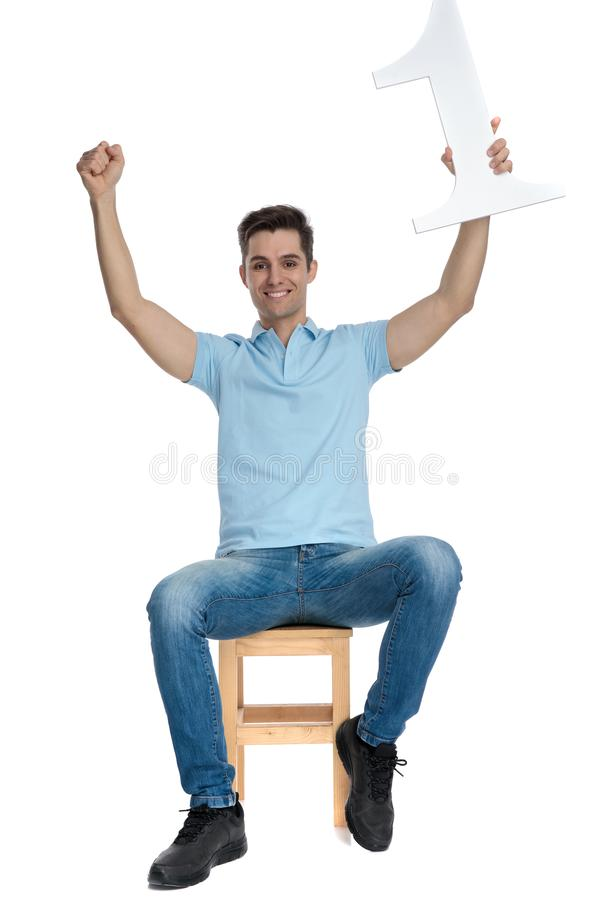 Positive casual guy celebrating and holding a number one. While smiling and sitting on a chair on white studio background stock photos
