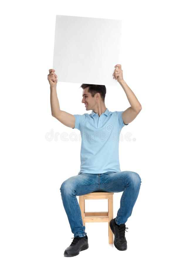 Positive casual guy holding an empty billboard above his head. And looking to the side while wearing a blue shirt and jeans, sitting on a chair on white studio royalty free stock photography