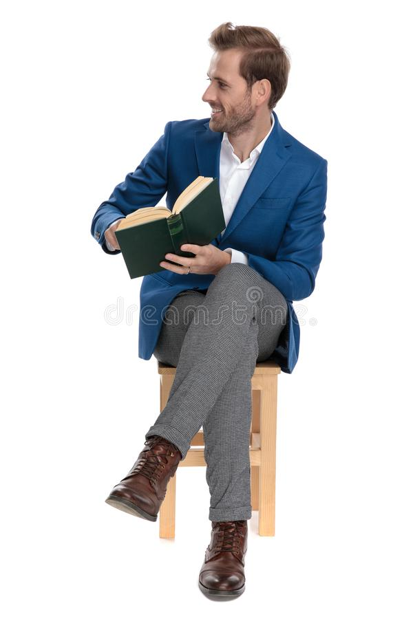 Positive casual guy presenting a book while smiling. And wearing a suit, sitting on a chair on white studio background stock photography