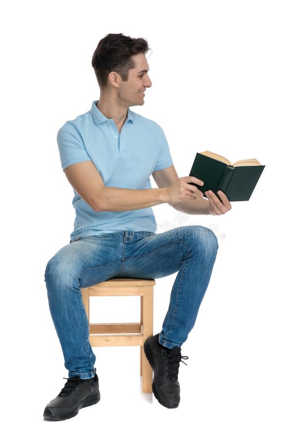 Positive casual man preseting a book to the side stock photo