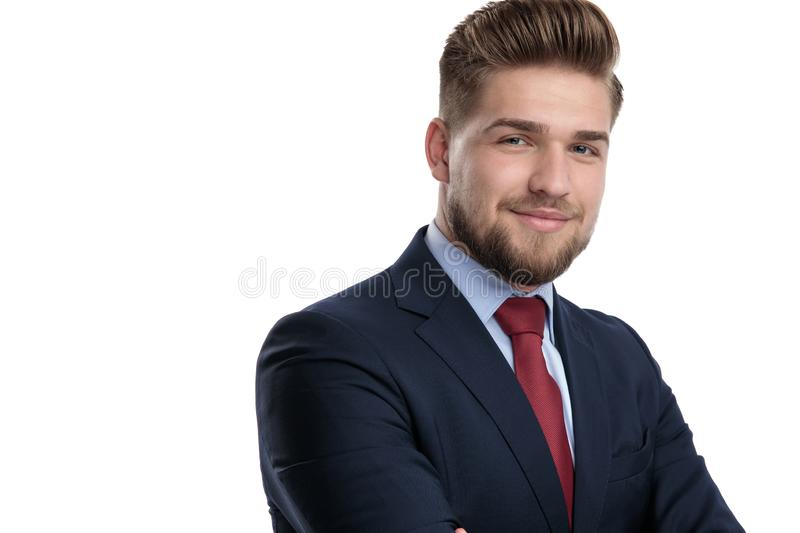 Positive casual man standing with his arms folded. While wearing a blue suit and smiling on white studio background stock photography