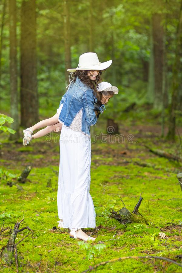 Positive Caucasian Couple of Mother and Little Daughter Playing Together in Green Summer Forest. Family Ideas and Concepts. Positive Caucasian Couple of Mother royalty free stock image