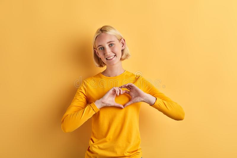 Positive charming beautiful woman makes heart gesture with fingers. Isolated yellow background, studio shot, positive feeling and emotion , I love you stock photography