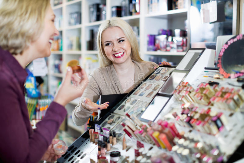 Positive charming woman customer chooses cosmetics royalty free stock images
