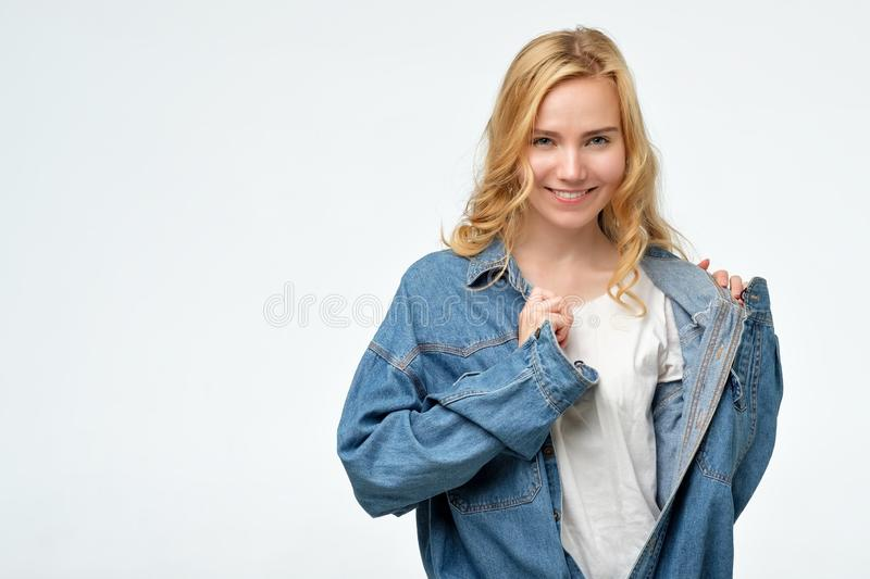 Positive cheeky caucasian blonde girl in jeans jacket smiling at camera royalty free stock image
