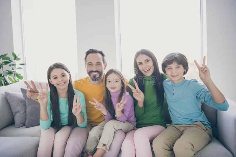 Positive cheerful family five people dad mom sit cozy couch three kid preteen little boy girl make v-sign enjoy harmony royalty free stock photo
