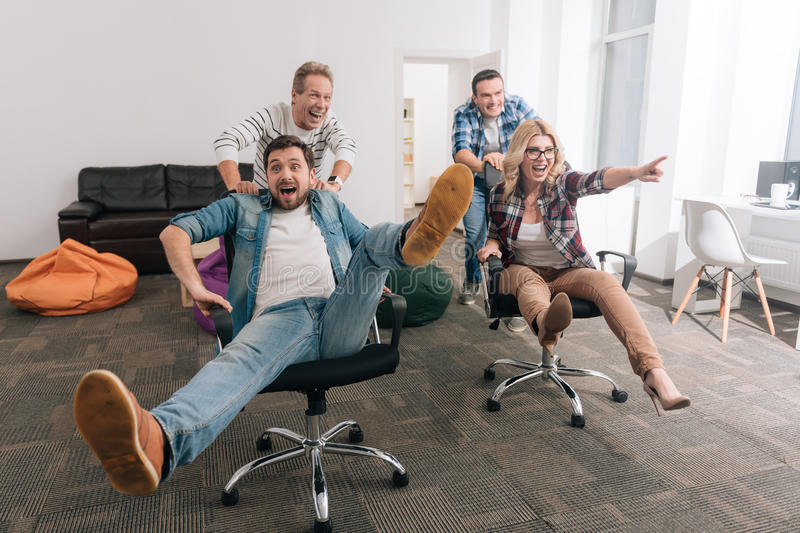 Positive cheerful men pushing office chairs royalty free stock photography