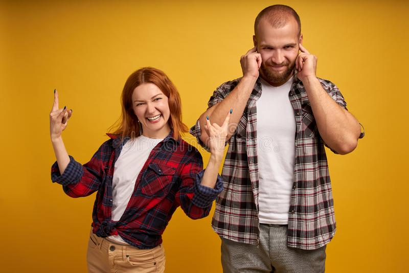 Positive cheerful young woman makes rock n roll gesture, exclaims very loud, annoyed man doesnt like music she listens, plugs ears stock image