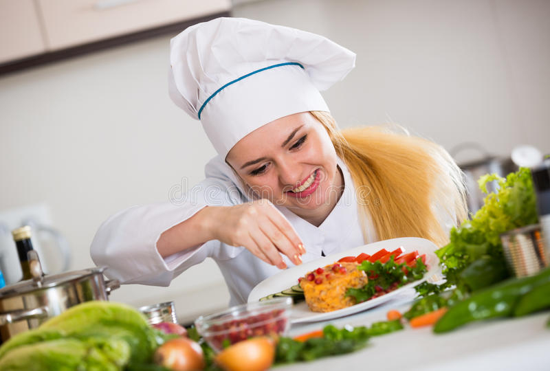Positive chef posing with vegetable mix and cheese. Professional chef cooking vegetable mix with cheese at kitchen table royalty free stock image