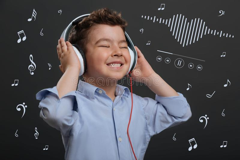 Positive child closing his eyes while listening to music royalty free stock photos