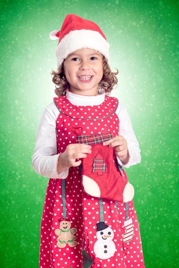 Positive Christmas child. Portrait of positive little child holding Christmas sock royalty free stock photography