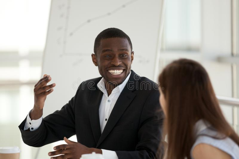 Positive colleagues communicating sitting in office desk. Diverse multiracial colleagues communicating, focus on black businessman talking with young caucasian stock photography