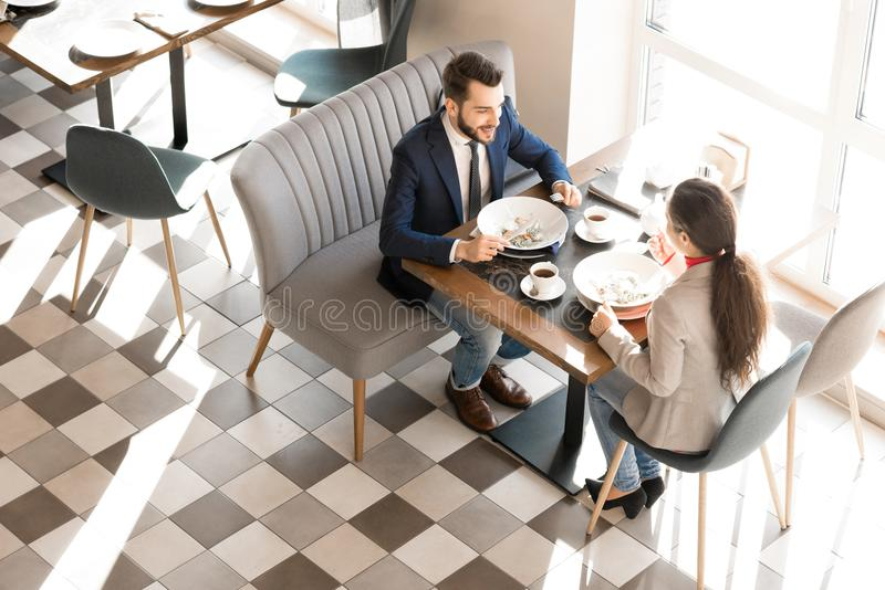 Positive colleagues enjoying lunch time in business cafe. Cheerful excited handsome young businessman eating salad and talking to colleague while they discussing royalty free stock photos