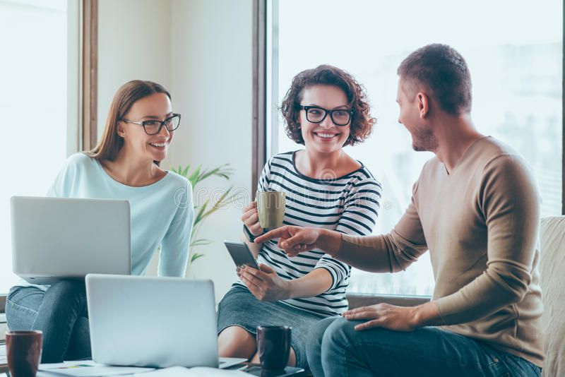 Positive colleagues sitting in the office. Positive atmosphere. Pleasant delighted smiling colleagues sitting at the table and talking while expressing gladness royalty free stock photo
