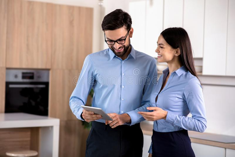 Positive colleagues using tablet in the kitchen royalty free stock images