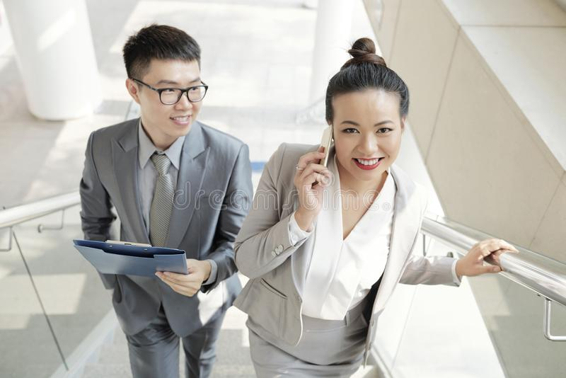 Positive colleagues. Young businessman looking at his cheerful pretty Vietnamese coworker stock image