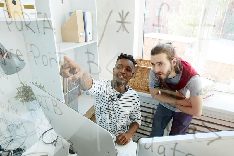 Skilled software engineers discussing coding algorithm royalty free stock photo