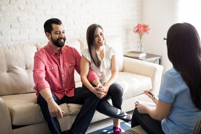 Positive consultation with psychologist. Hispanic couple sitting close to each other and holding hands while looking at their therapist stock images