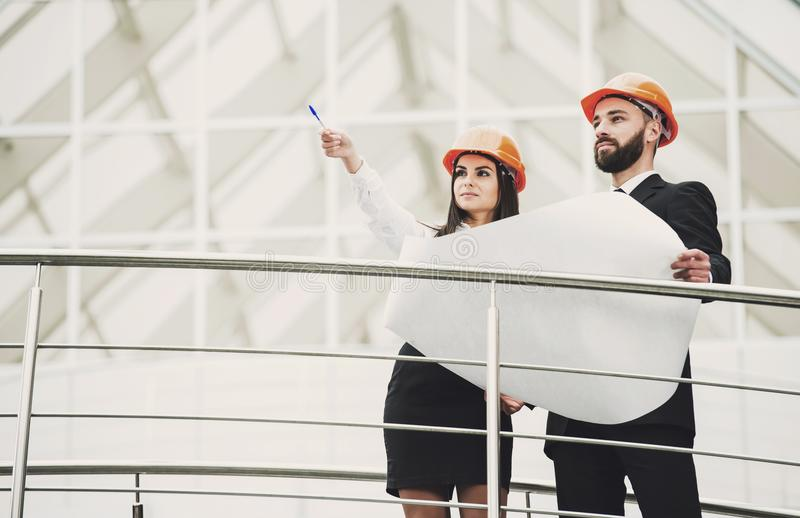 Positive contented professional architects looking up while talking about the project. royalty free stock image