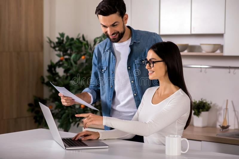 Positive couple of entrepreneurs sitting at home stock photo