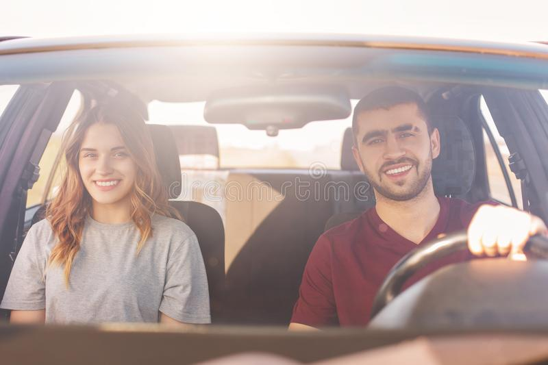 Positive couple has trip in car, looks positively at camera, being satisfied with journey, enjoy high speed. Cheerful male and his stock image