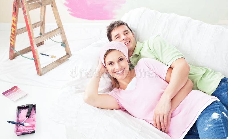 Positive Couple Lying On A Sofa After Painting Royalty Free Stock Image