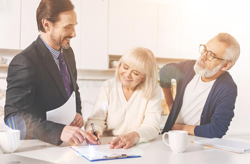 Positive couple signing papers with insurance agent. Commonh decision. Cheerful lovign aged couple smiling and meeting with real estate agent while signing royalty free stock photo