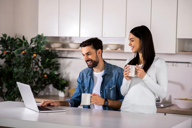 Positive couple using laptop in the kitchen royalty free stock photo