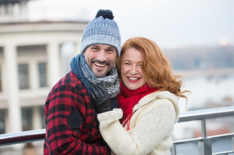 Positive couple wearing warm clothes and smiling happily. Cheerful relaxed couple standing outdoors in warm winter clothes and smiling while hugging royalty free stock photo