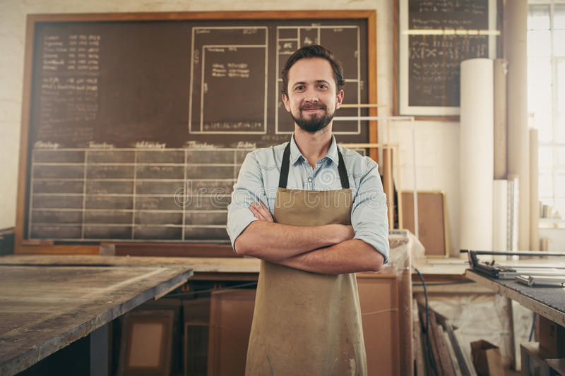 Positive craftsman in his workshop with arms folded royalty free stock photos