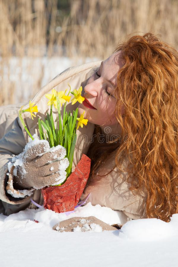 Positive curly haired woman enjoying pleasant fragrance of narcissus while lying in snowdrift royalty free stock photos