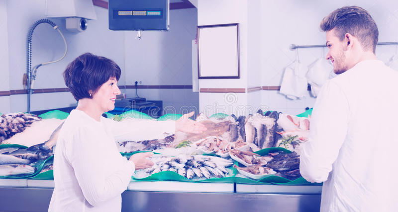 Positive customers choosing seafood in store royalty free stock images