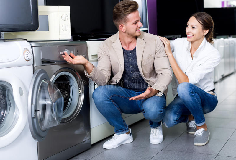Positive customers looking at laundry machine stock images