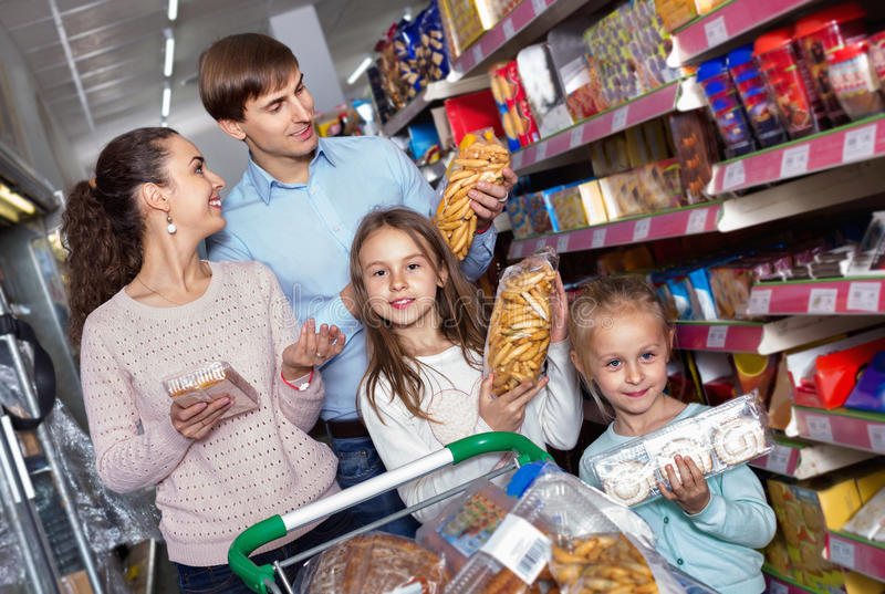 Positive customers with small children purchasing shortcakes stock image