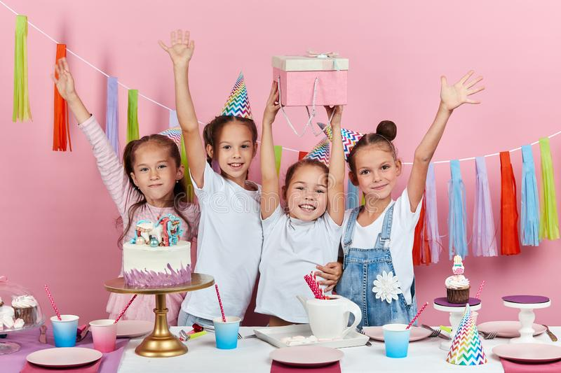 Positive cute girls raising their arms celebrating birthday royalty free stock images