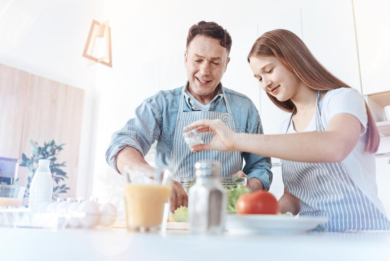 Positive dad and daughter during meal preparation stock photography
