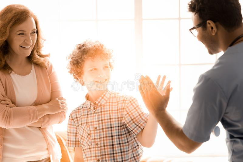 Positive delighted boy looking at his doctor royalty free stock images