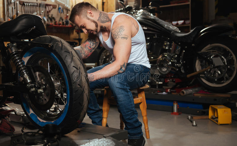 Positive delighted brutal biker fixing wheel royalty free stock images