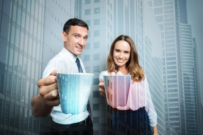 Positive delighted colleagues holding cups with tea. Warm drink. Positive delighted nice colleagues smiling and holding cups of tea while having a break together stock photo