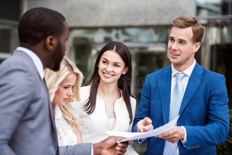 Positive delighted colleagues talking. Business look. Pleasant content colleagues standing near office building and working with papers while expressing joy royalty free stock image
