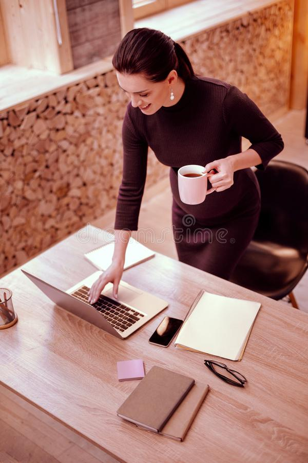 Positive delighted female person standing at her workplace royalty free stock photography