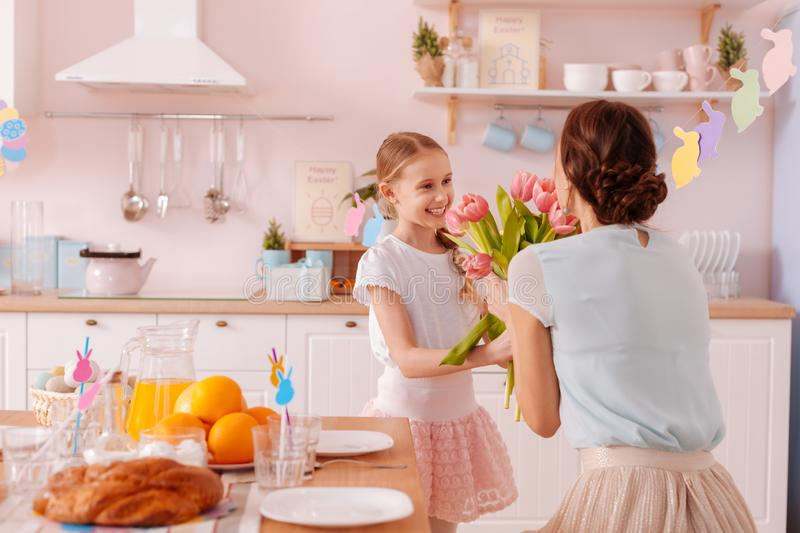 Positive delighted kid presenting flowers to her mom. Happy holidays. Cute teenager standing near table while looking at her mother stock image
