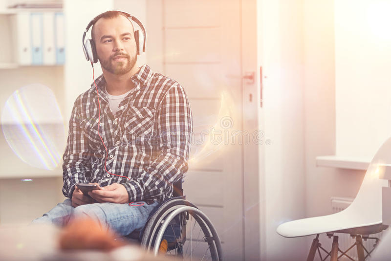 Positive delighted male person wearing earphones stock image