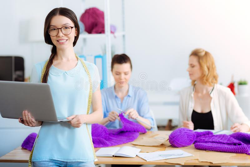 Positive delighted stylist holding her laptop royalty free stock images
