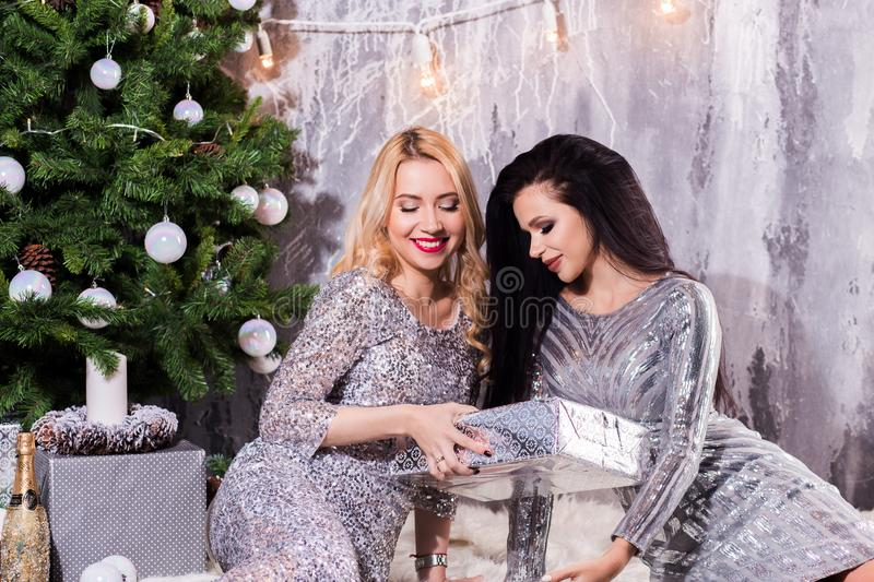 Positive delighted women giving each other Christmas gifts. New Year, holiday, celebration, winter concepts stock image