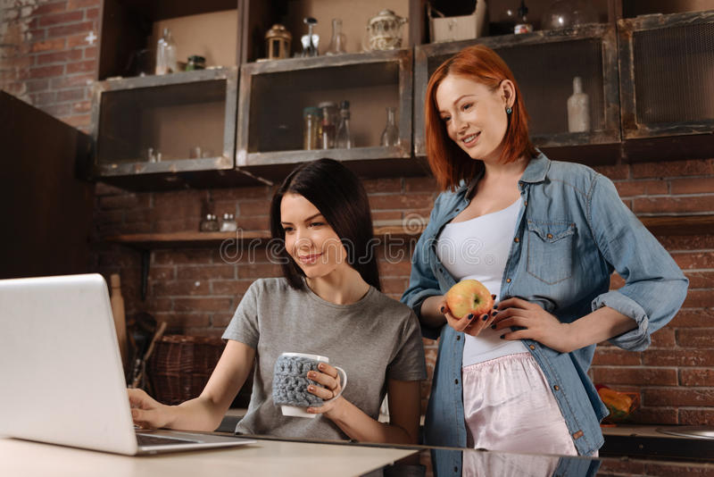 Positive delighted young brunette using laptop. Watch film. Cute smiling red haired female holding an apple in right hand keeping left hand on the belt while royalty free stock photos